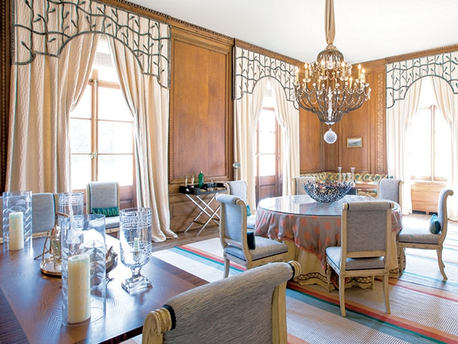The dining room exemplifies the home's luxurious wood paneling and extra-high ceilings, as well as its abundant sunlight.