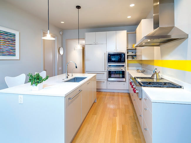 White cabinetry in the kitchen complements shelving found elsewhere in the home