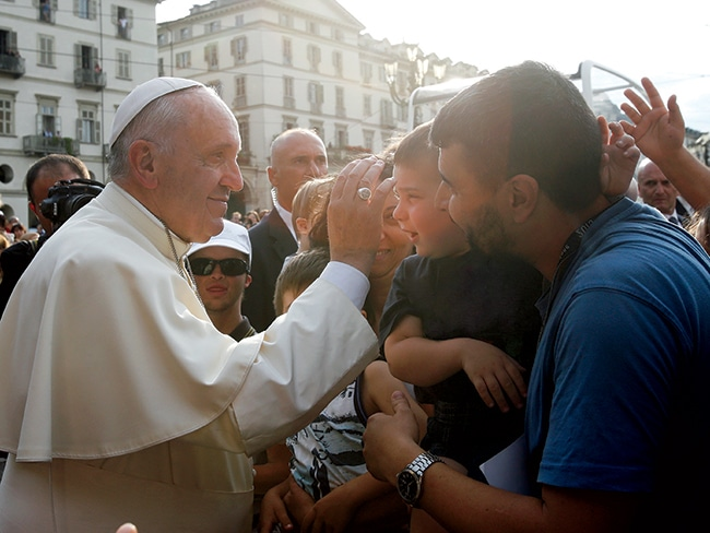The hand that gives: Pope Francis blesses a child during a two-day pastoral visit to Turin, Italy, in June.